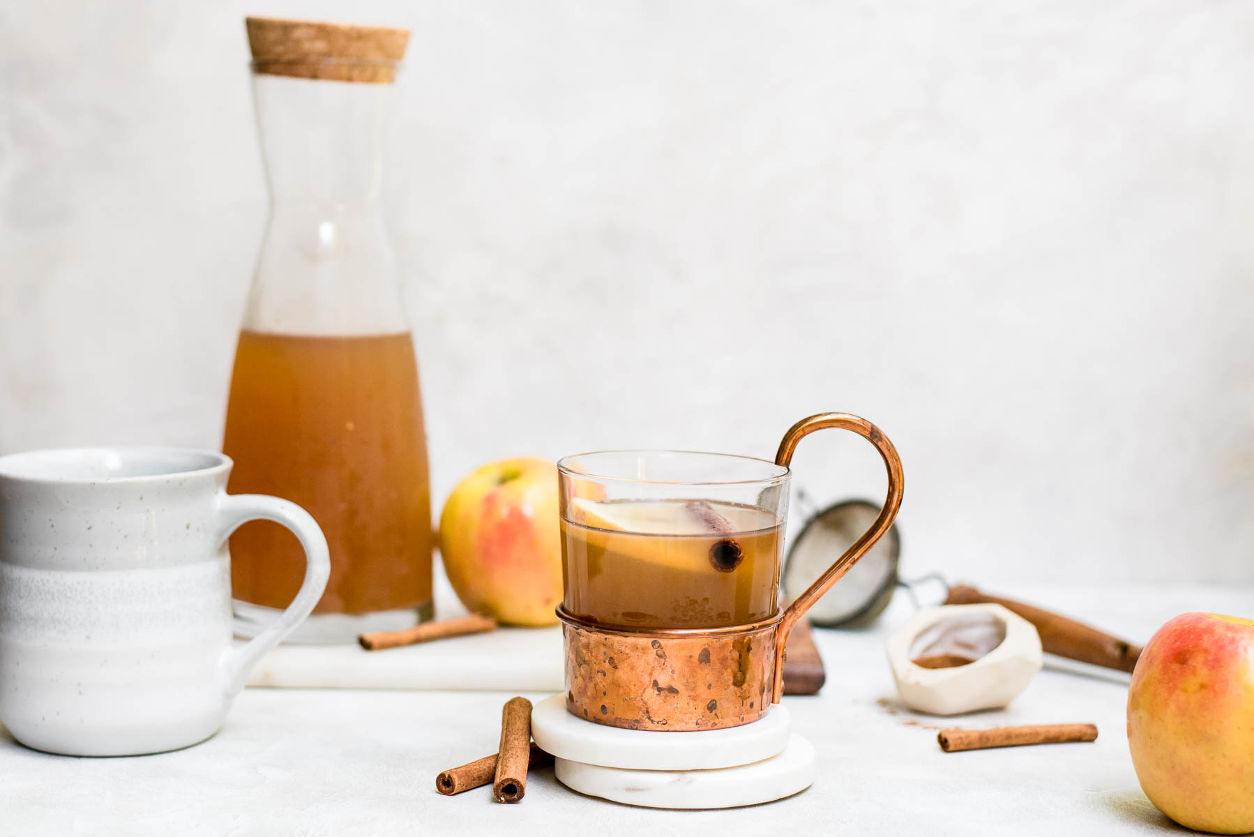 homemade apple cider on counter with white coasters, cinnamon sticks, and copper mug