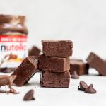 stacked nutella fudge with nutella jar in background