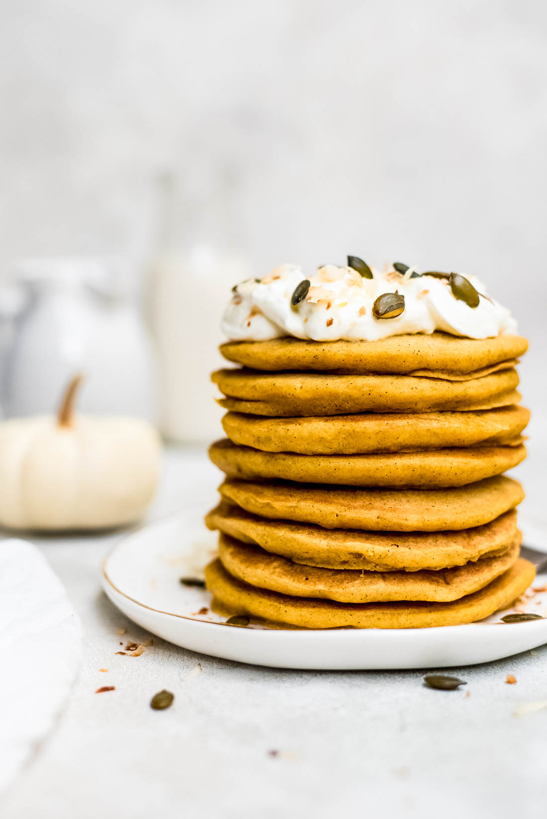 stacked pumpkin pancakes topped with whipped cream, toasted coconut, and pepitas