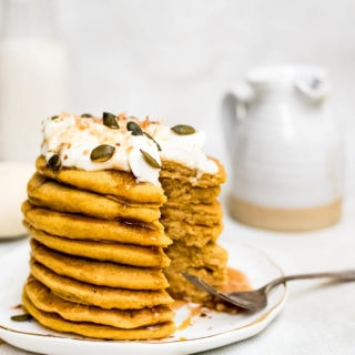 pumpkin pancakes drizzled with syrup being eaten close up