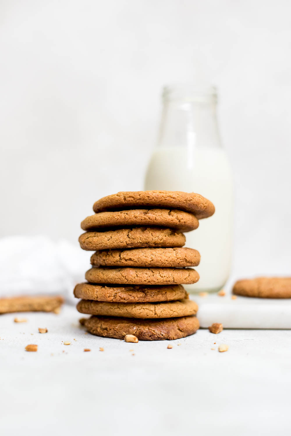 stacked 3 ingredient peanut butter cookies with glass of milk in background
