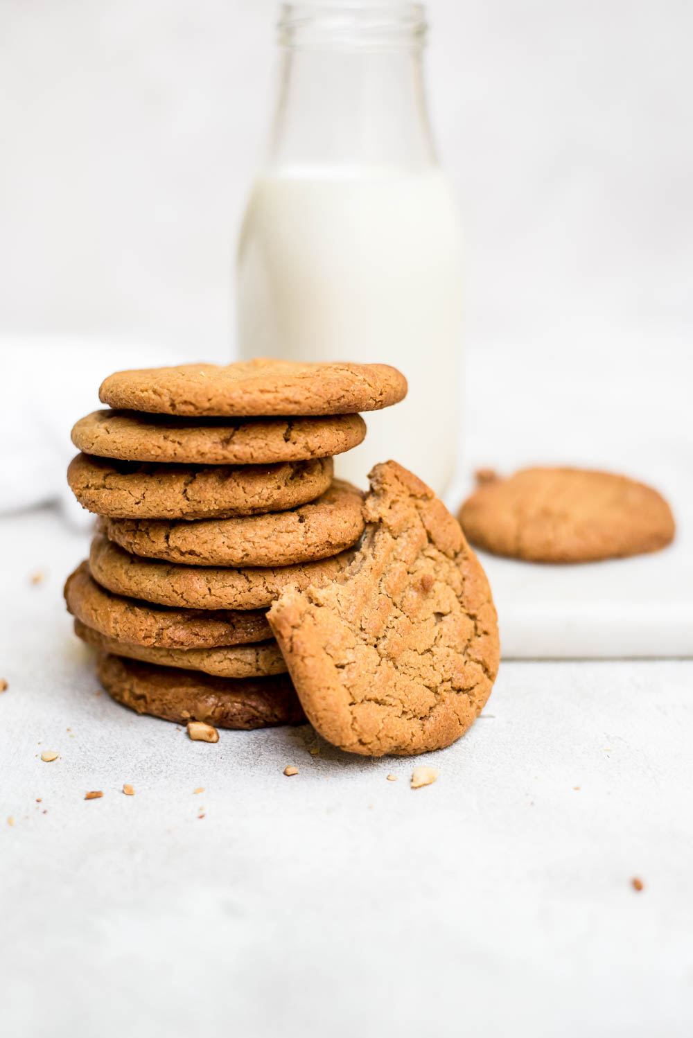 3 ingredient peanut butter cookies stacked with bite eaten from one cookie