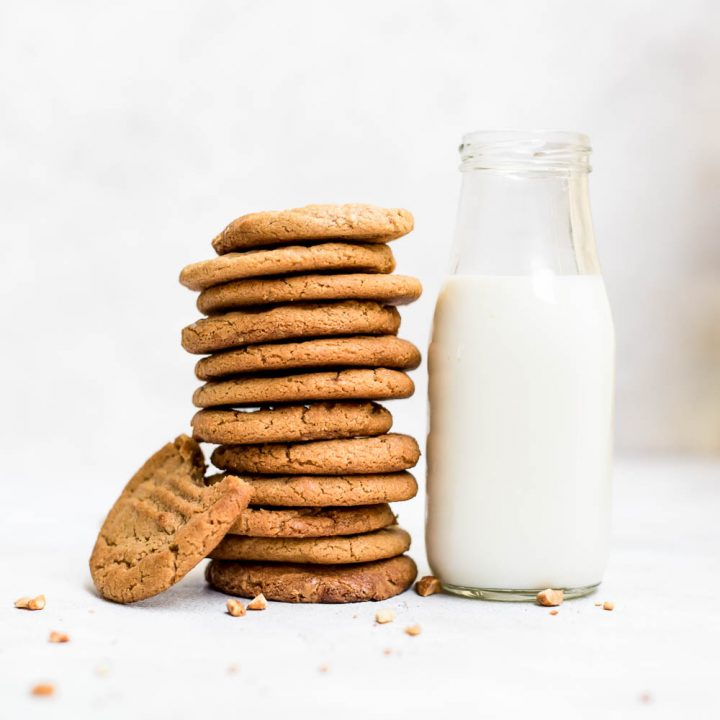 3 ingredient peanut butter cookies stacked next to jug of milk