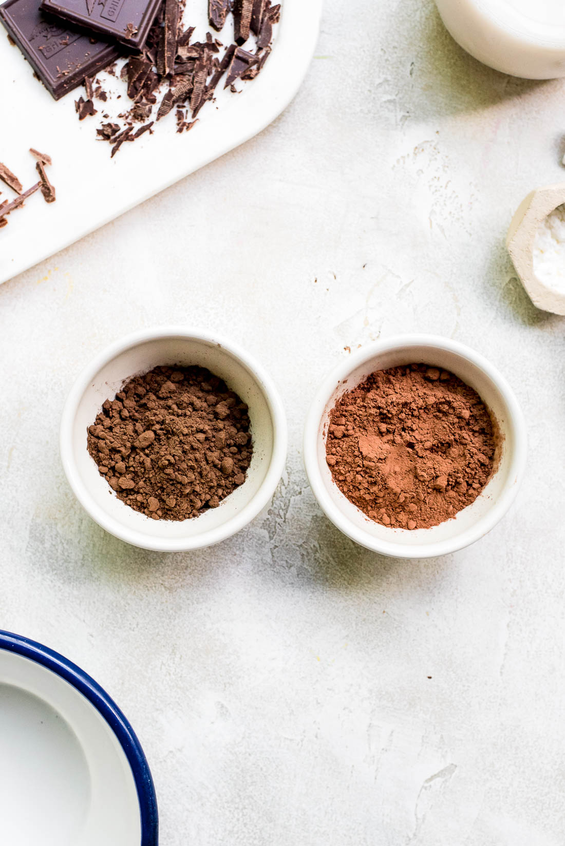 two small bowls filled with natural cocoa powder and dutch processed cocoa powder