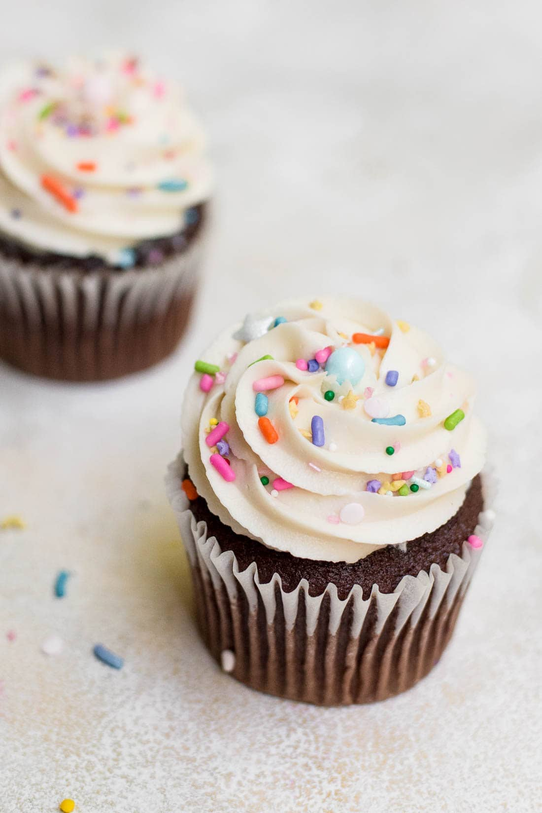 close up of cupcakes with vanilla buttercream frosting and sprinkles