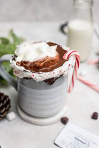 hot chocolate topped with whipped cream and mini candy cane