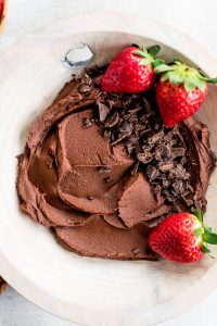 close up chocolate hummus in bowl topped with chocolate and strawberries
