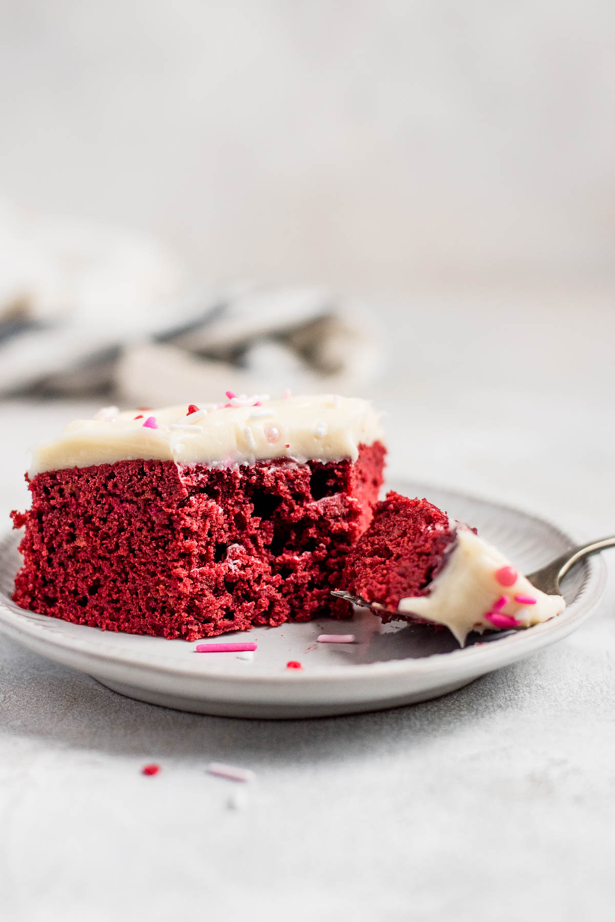 red velvet sheet cake on plate with piece missing