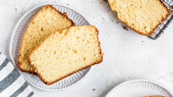 slices of vanilla pound cake on plates and being sliced