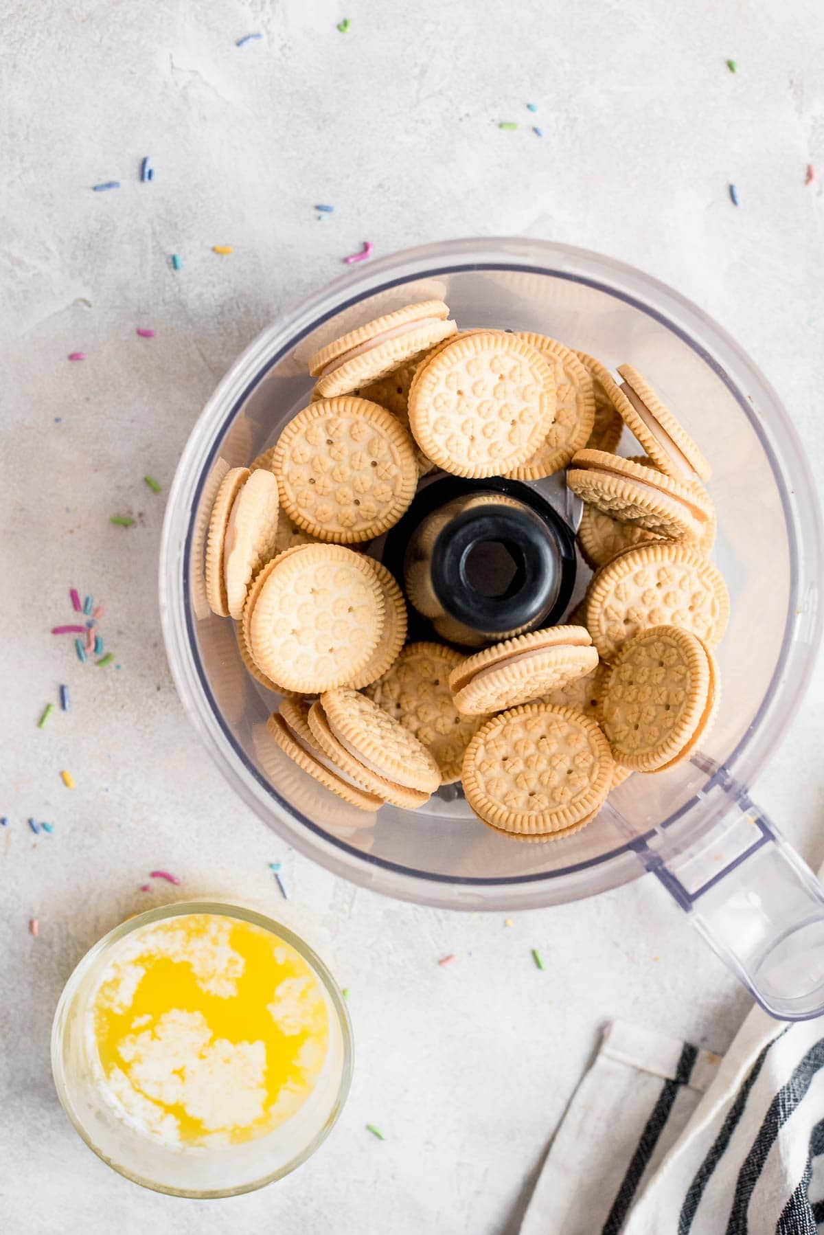 Oreos in food processor next to small glass bowl of melted butter