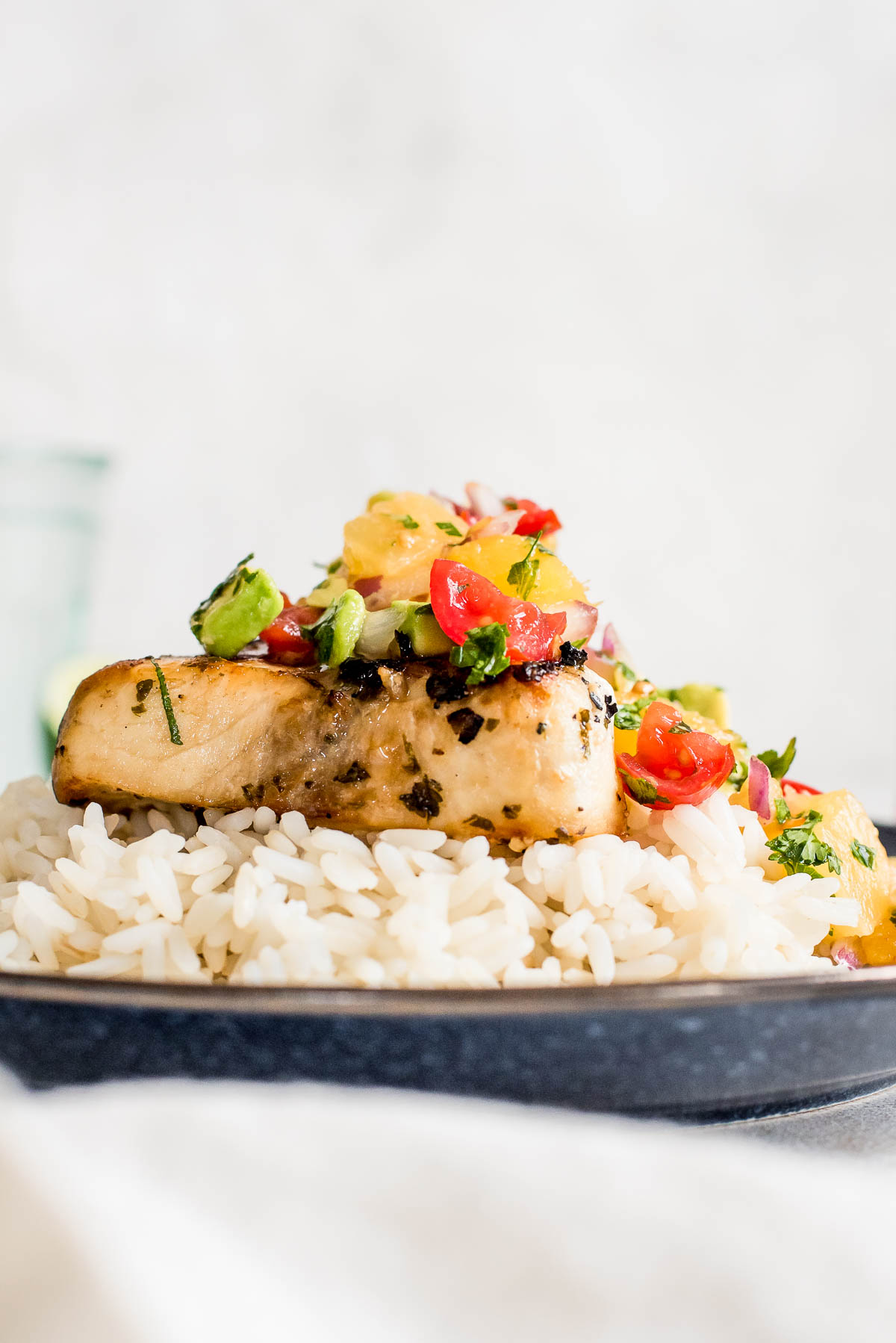 close up of grilled swordfish on top of rice finished with pineapple salsa