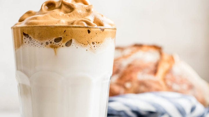 whipped coffee in glass with loaf of bread in background