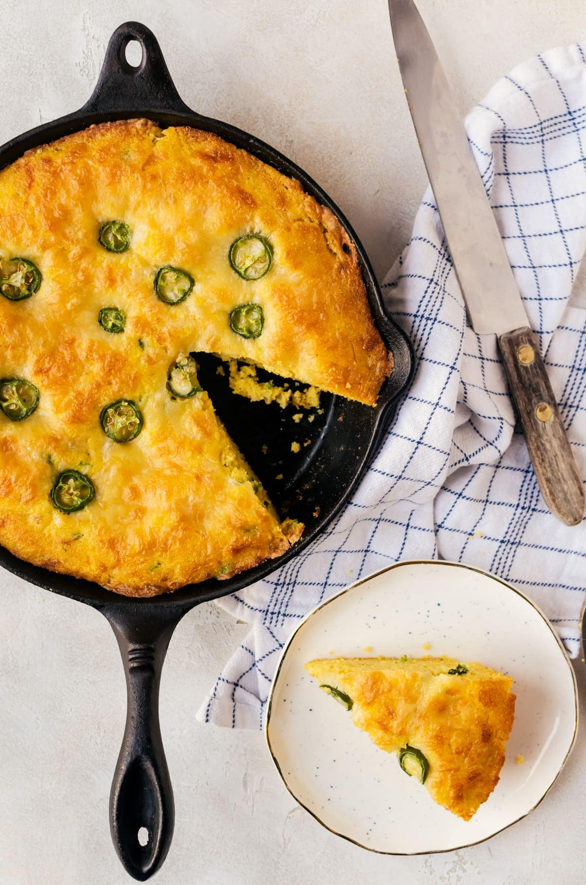 cornbread in skillet with slice on white plate