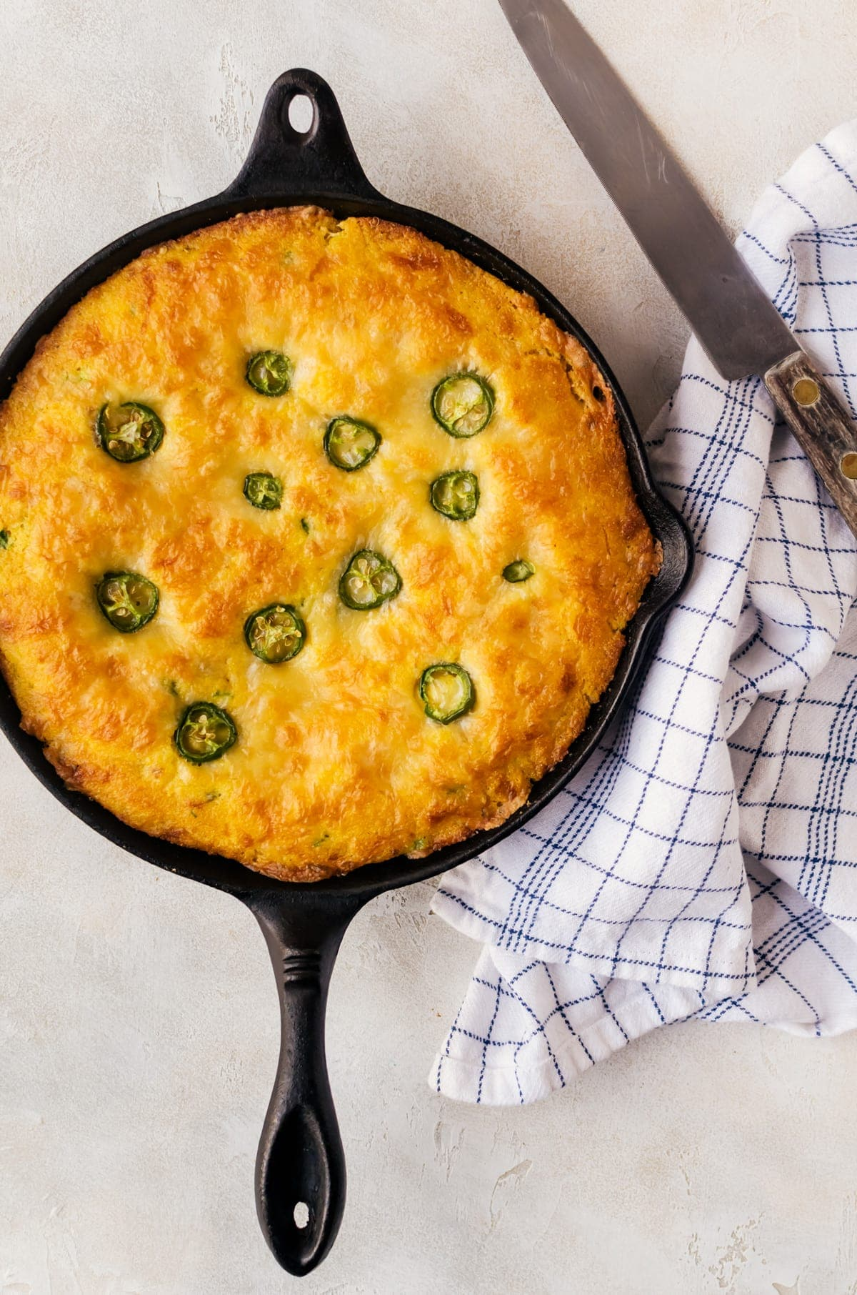 cheddar jalapeno cornbread in skillet on table with kitchen towel
