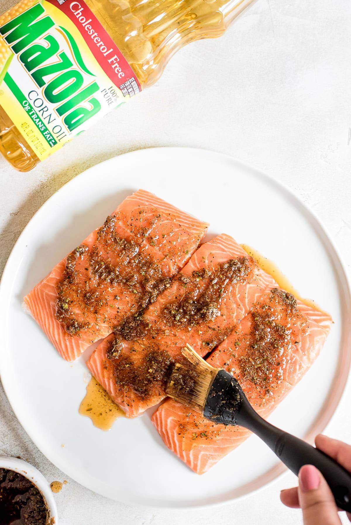 raw salmon being coated in marinade