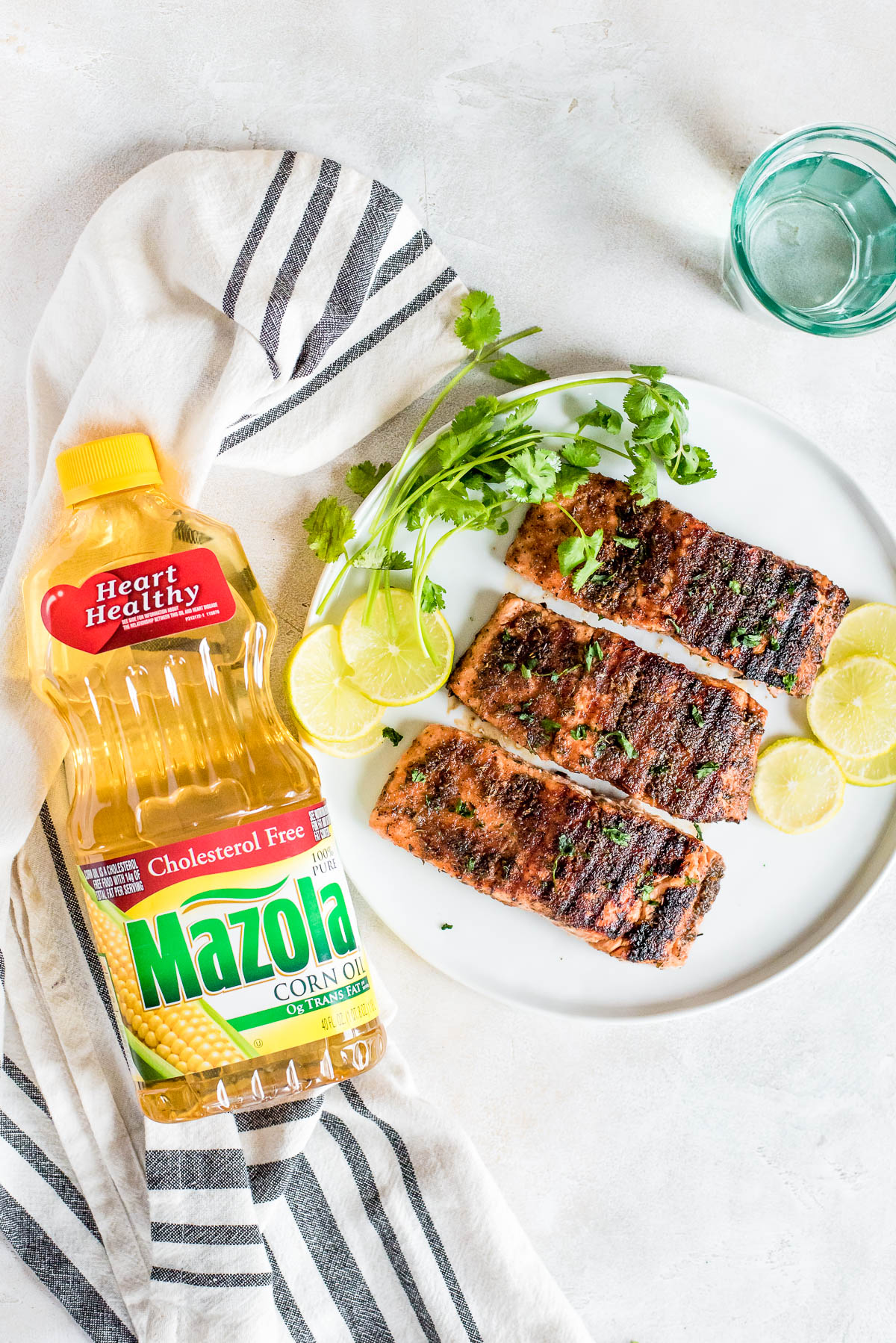 grilled salmon on plate next to bottle of mazola corn oil