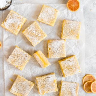 lemon bars on parchment paper dusted with powdered sugar