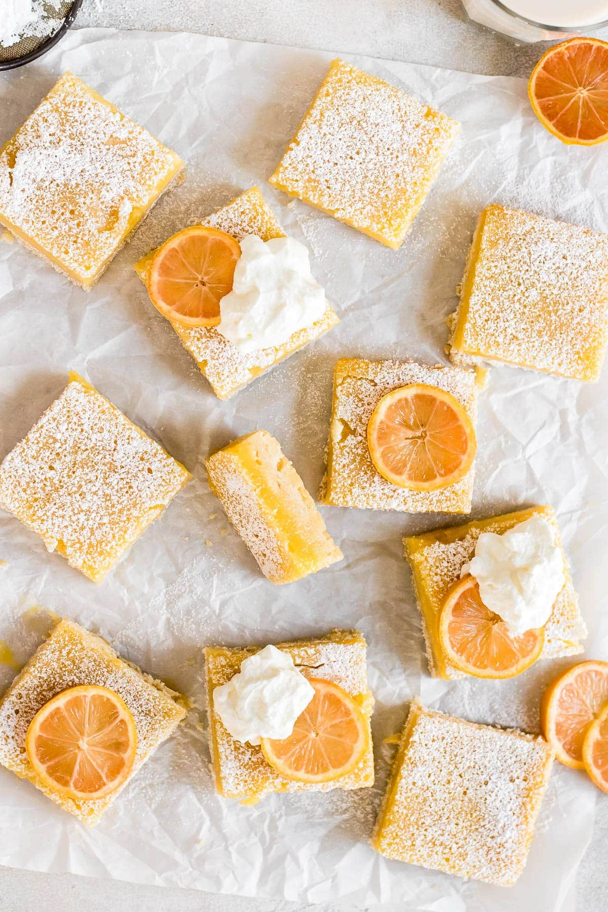 close up of lemon bars topped with whipped cream and sliced lemons