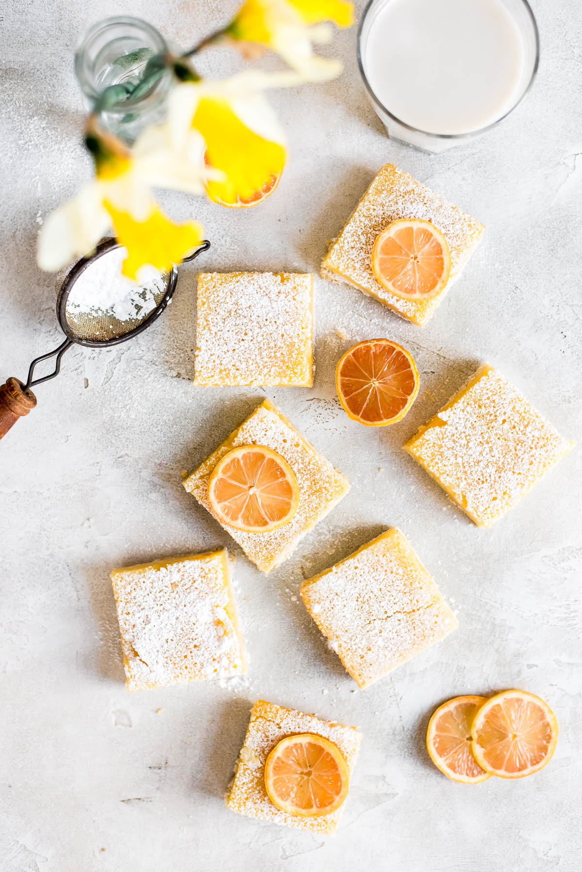 lemon bars topped with powdered sugar and lemons