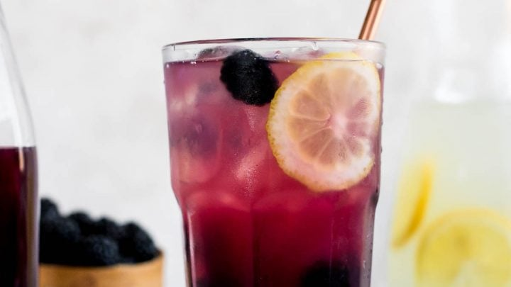 blackberry lemonade in a glass next to blackberries and syrup