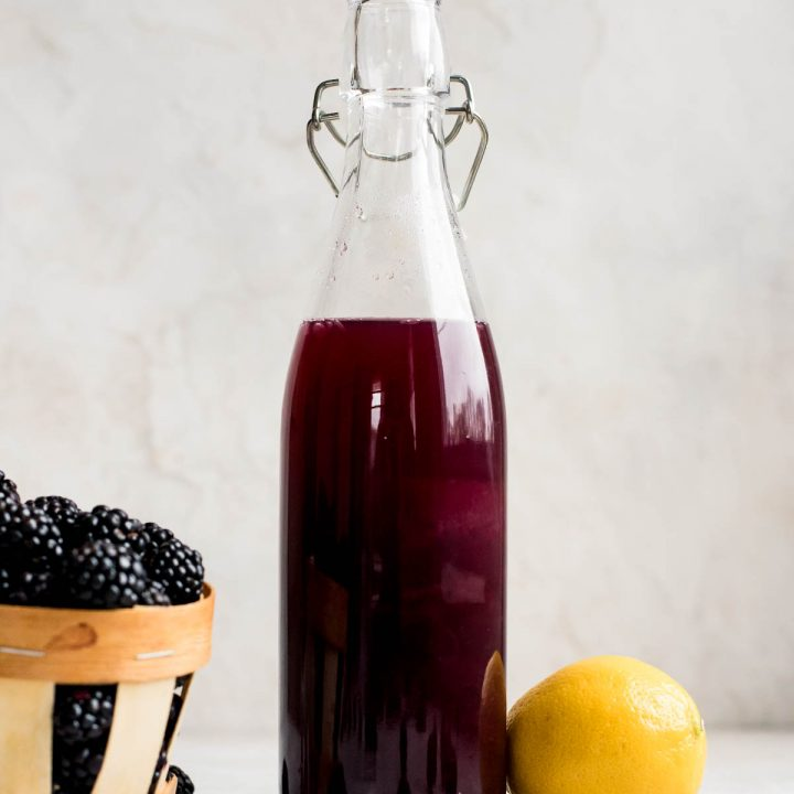blackberry syrup in bottle next to blackberries and lemon