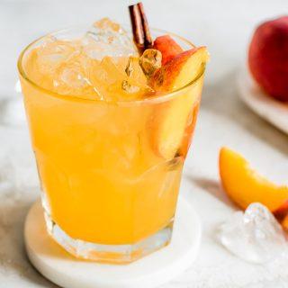 close up shot of moonshine with peach slice and cinnamon stick garnish