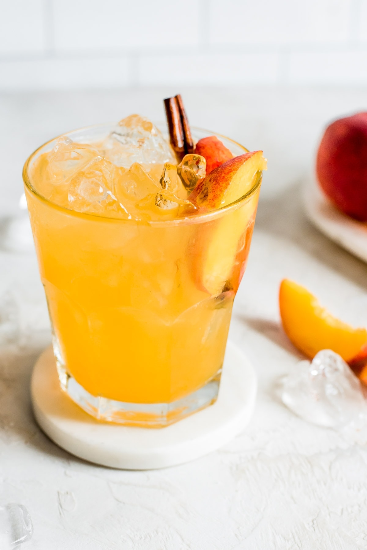 close up shot of moonshine with peach slice and cinnamon stick garnish