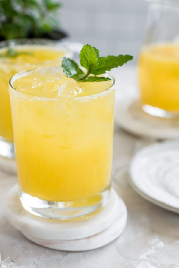 close up glass of mango mojito with mint sprig