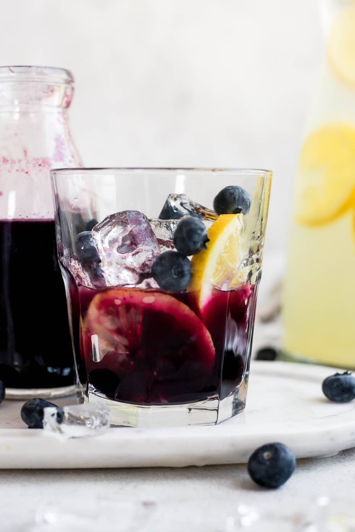 blueberry syrup with blueberries and sliced lemons in glass