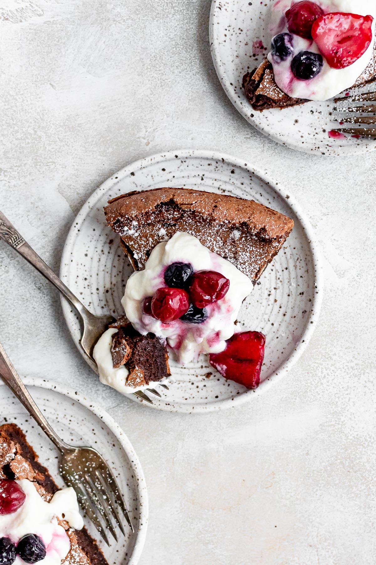 slice of cake on white plate topped with whipped cream and berries