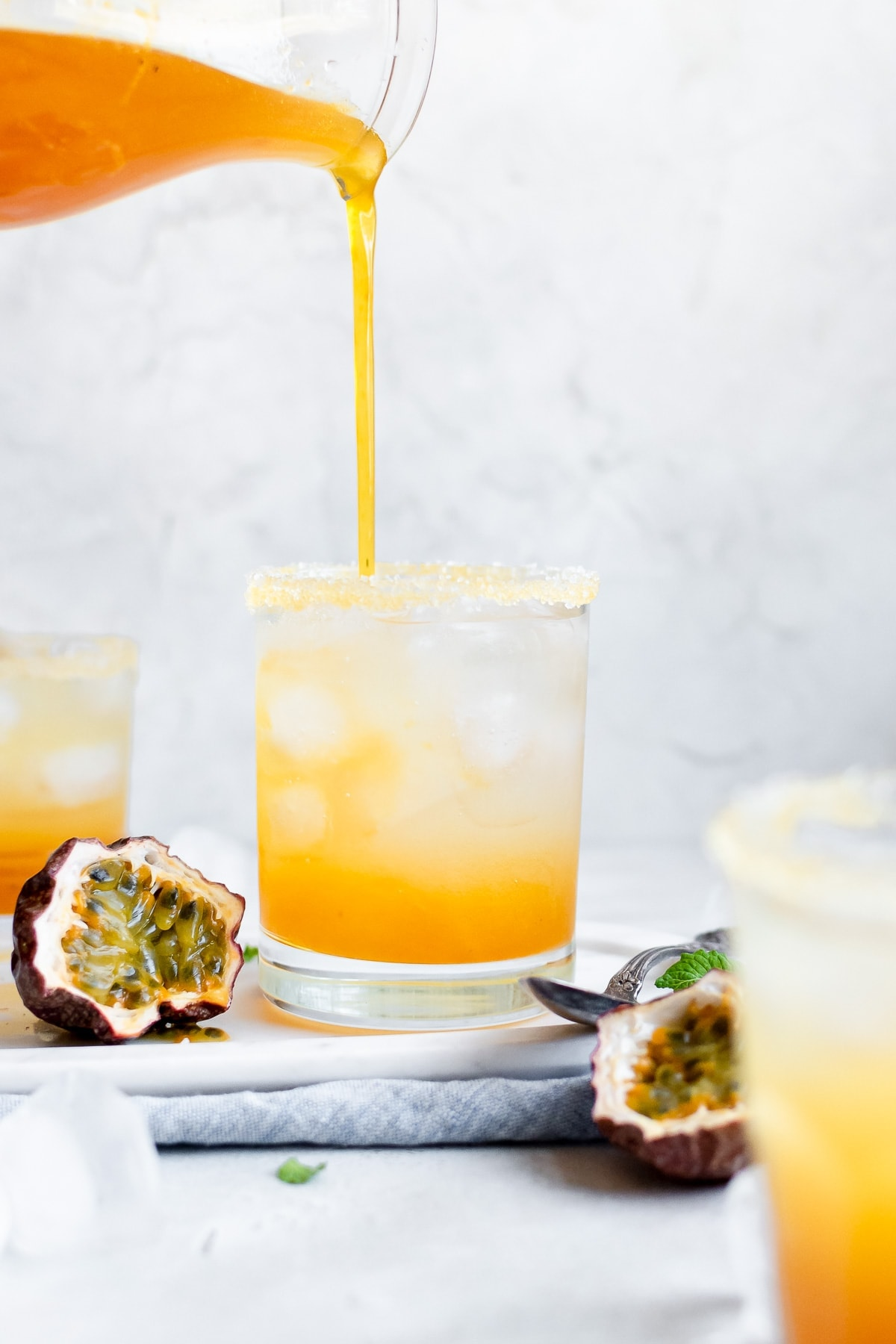 pouring passion fruit syrup into margarita