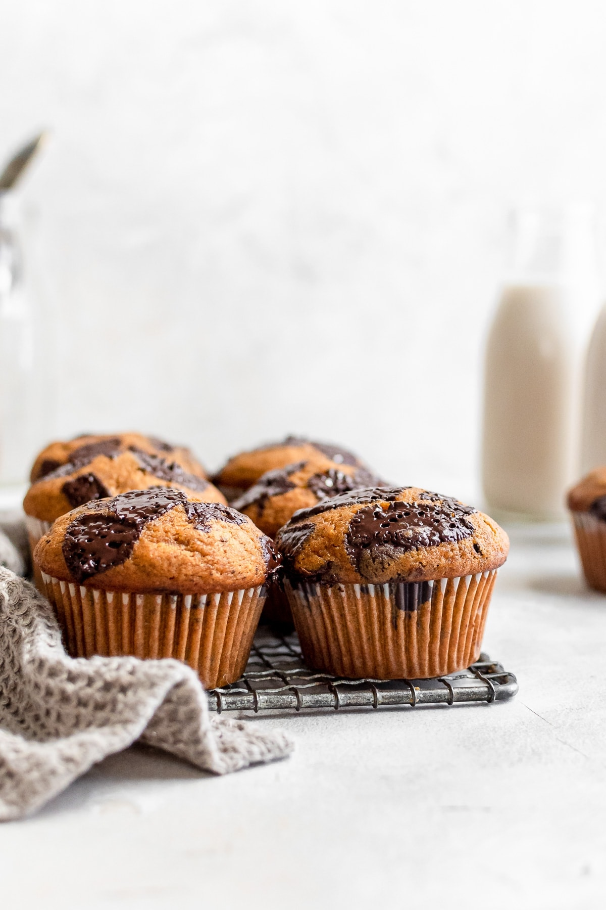 pumpkin muffins on wire rack with milk bottle in background