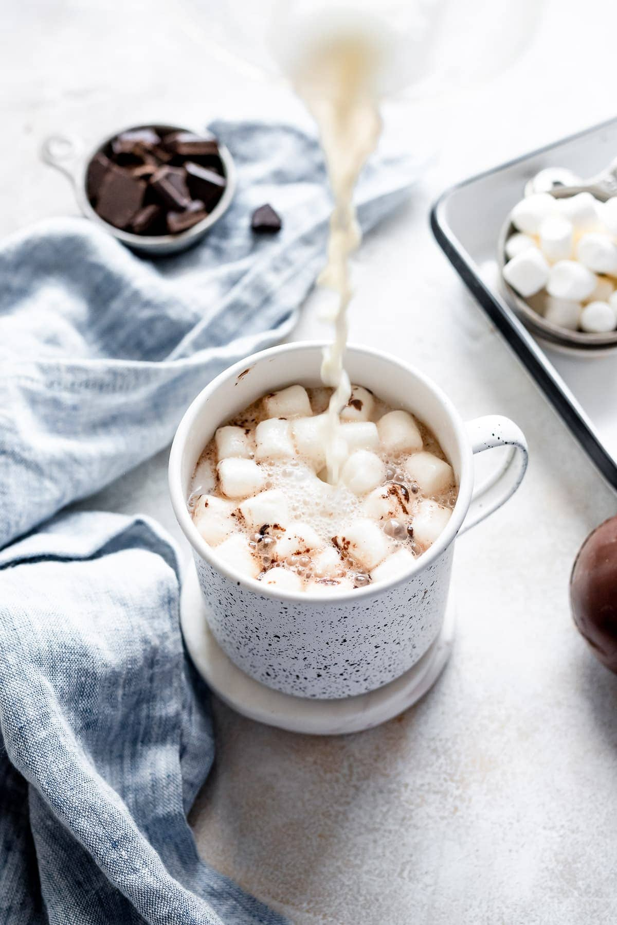 milk pouring oer hot chocolate and marshmallows