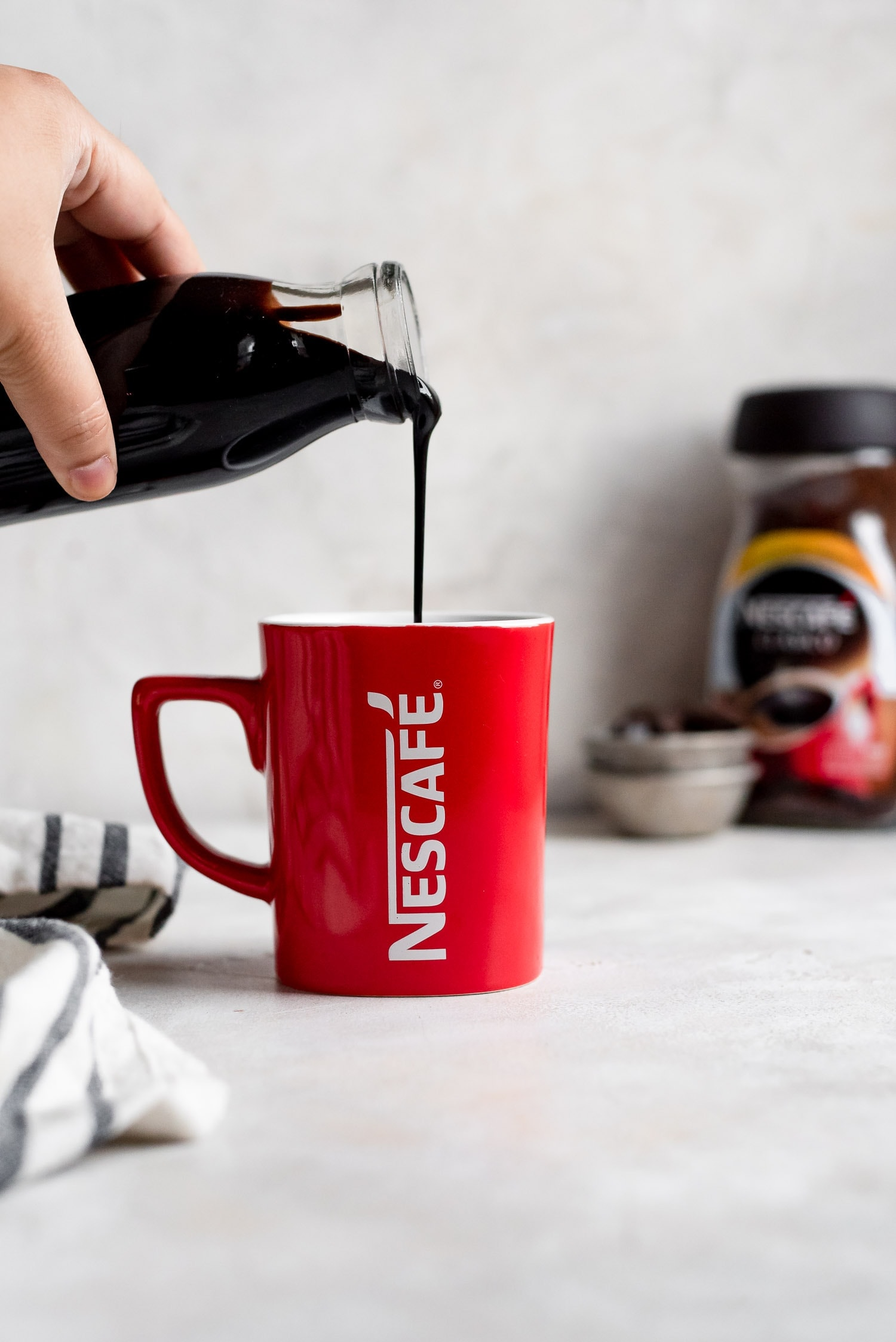 chocolate syrup being poured into mug of coffee