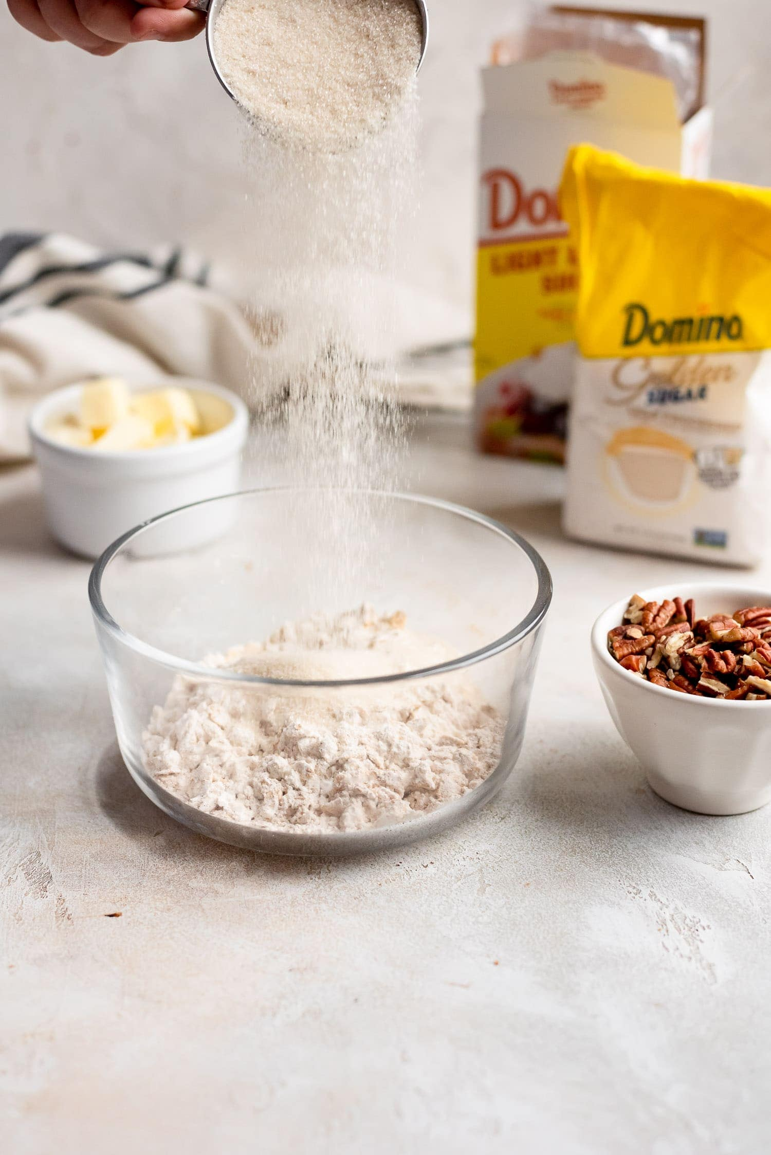pouring sugar into bowl to make streusel