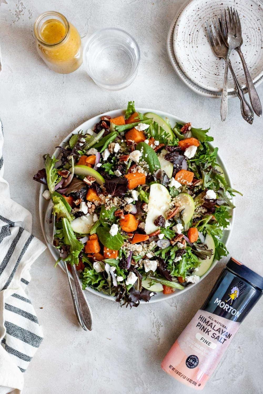 harvest  salad on serving plate next to plates, forks, and salt