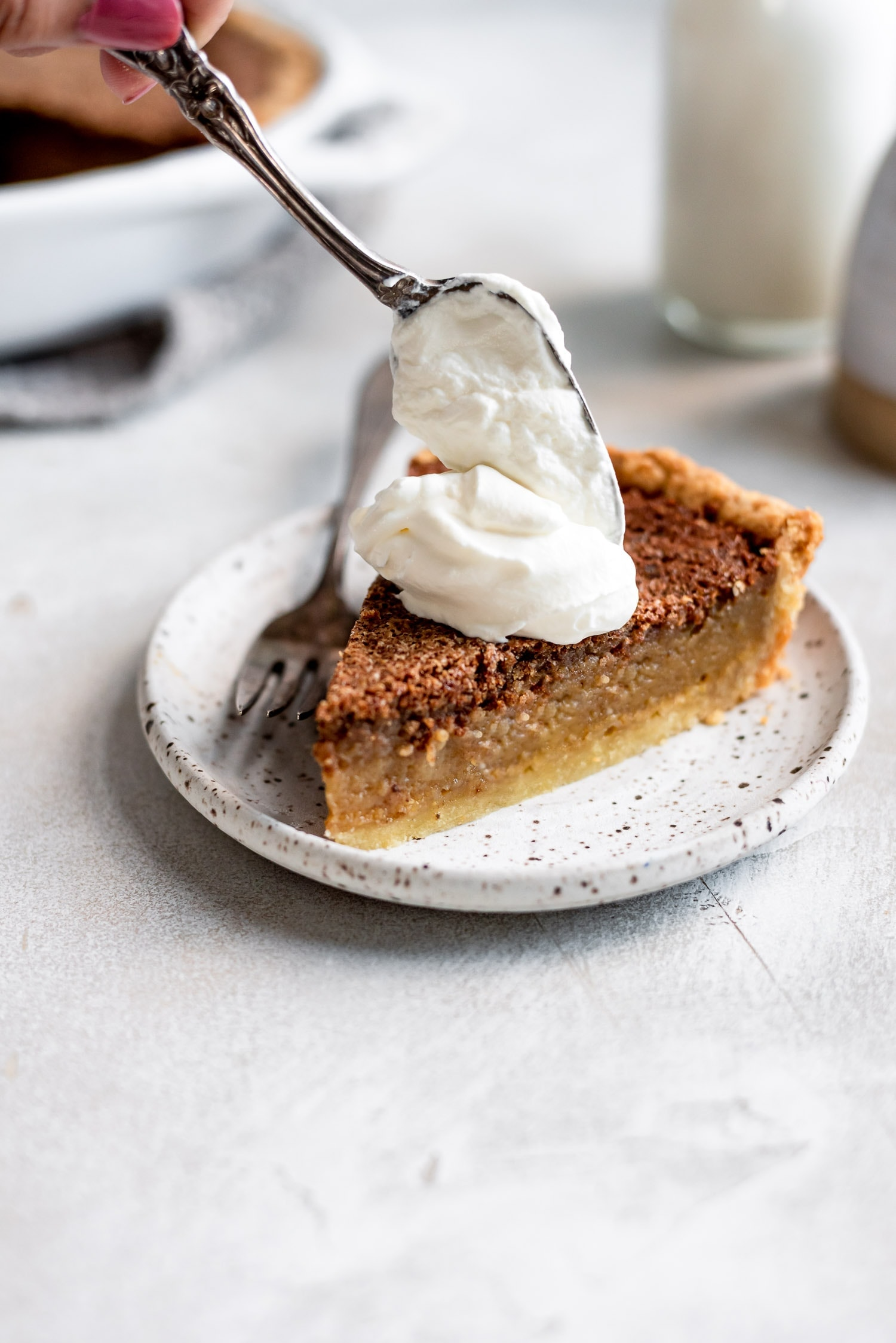 hand dolloping whipped cream onto slice of pie