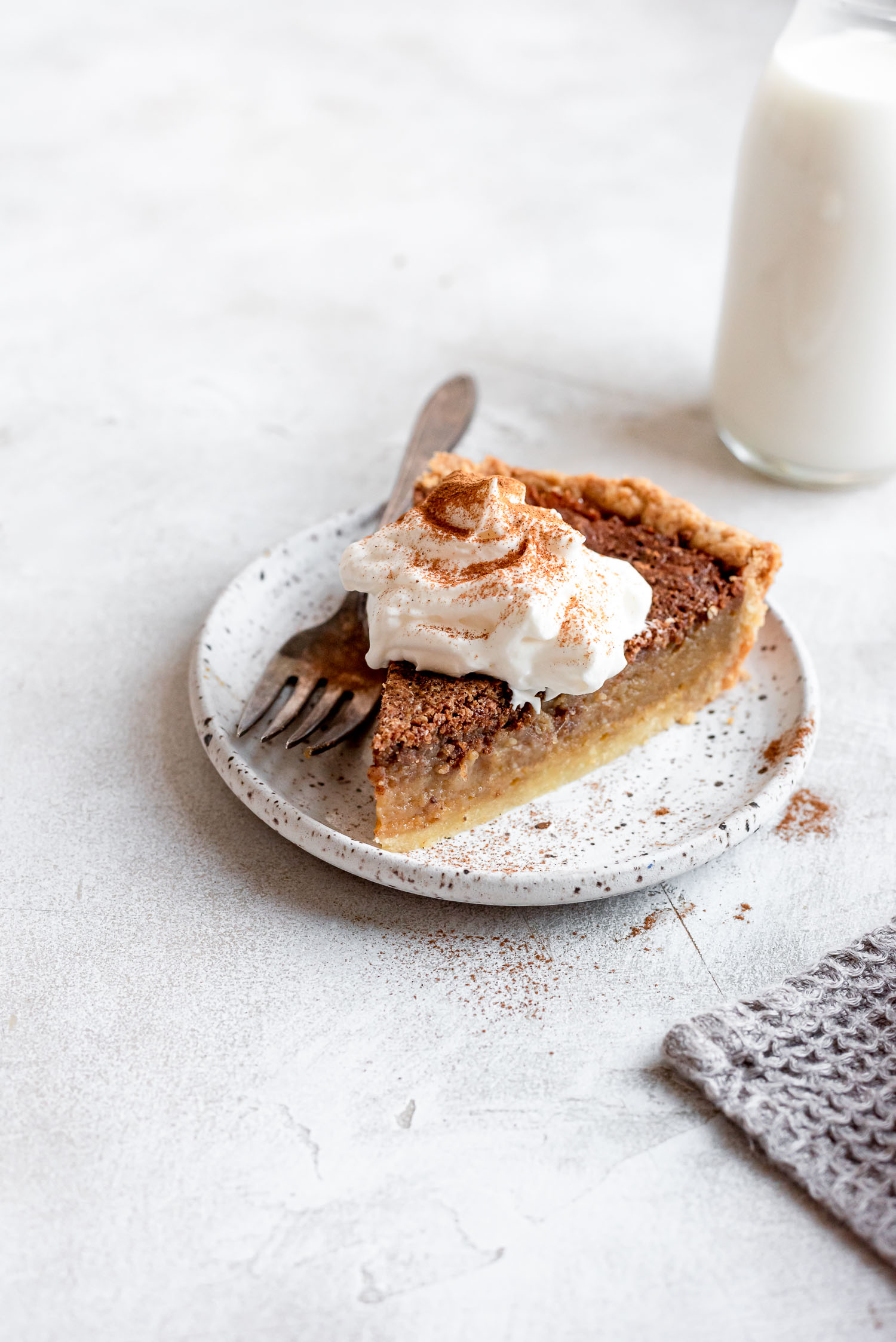 chess pie topped with whippede cream and cinnamon on white plate with fork