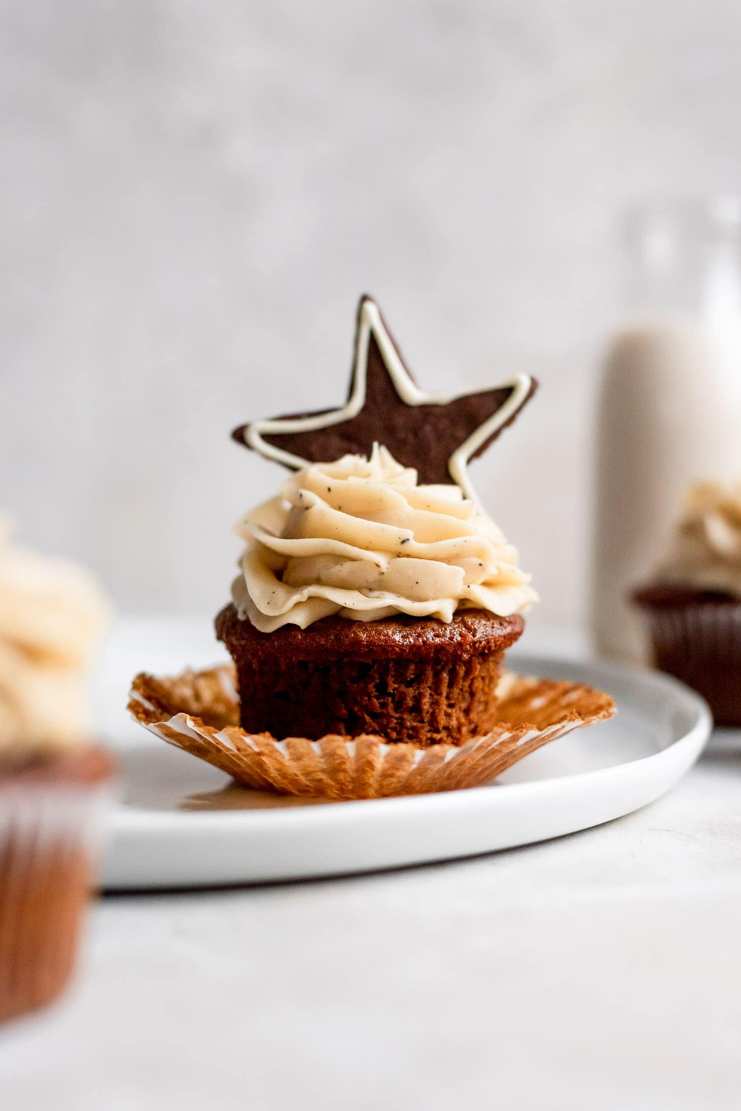 cupcake with wrapped peeled down topped with star gingerbread cookie