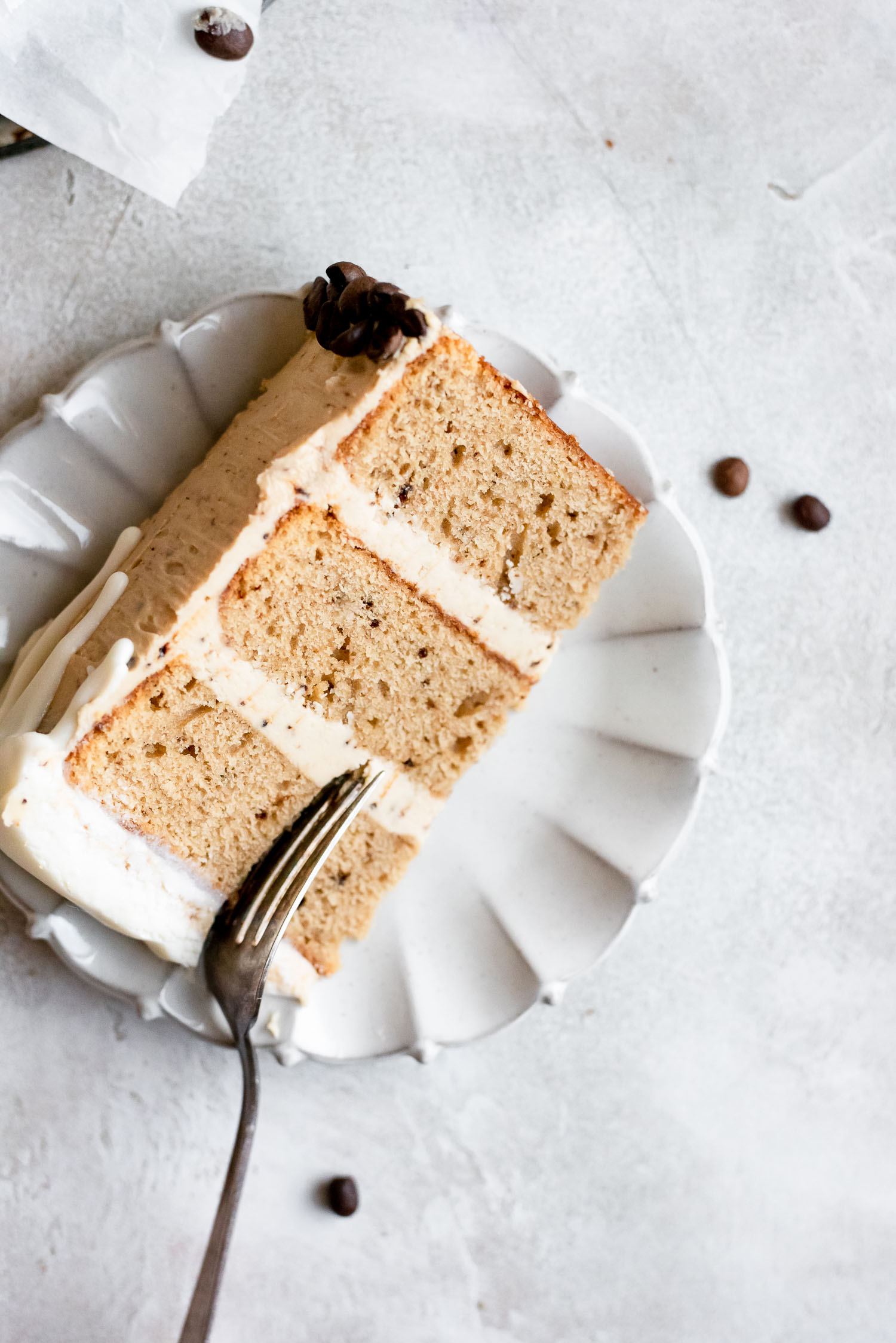 white chocolate mocha cake slice on white ruffle-rimmed plate with fork cutting into cake