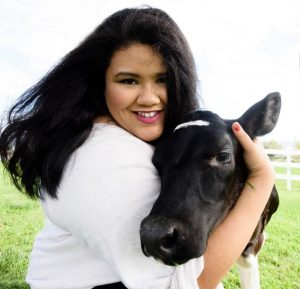 headshot of author with a cow