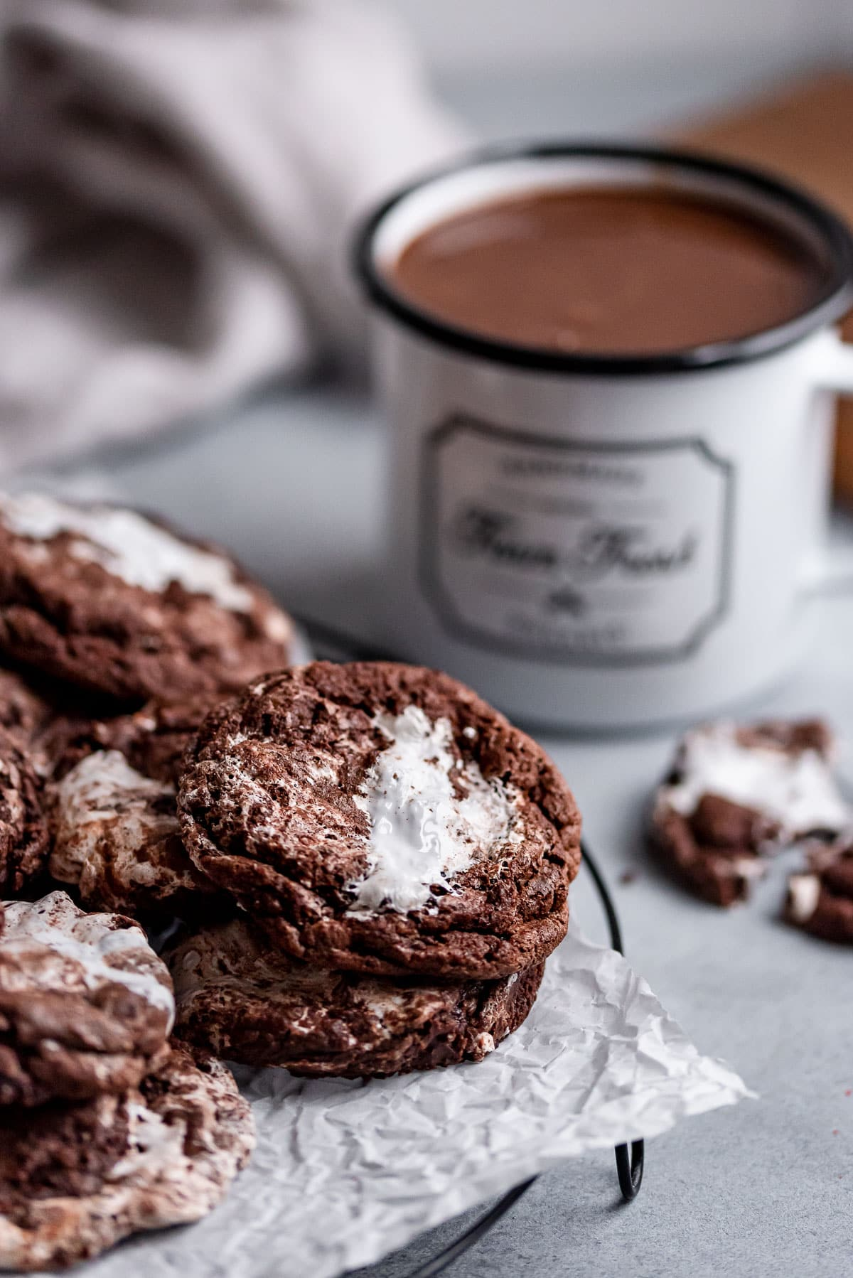 hot chocolate cookies stacked on wire rack next to mug of hot chocolate