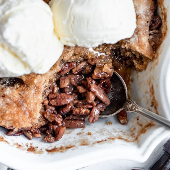 overhead close up pecan pie cobbler topped with ice cream in pan