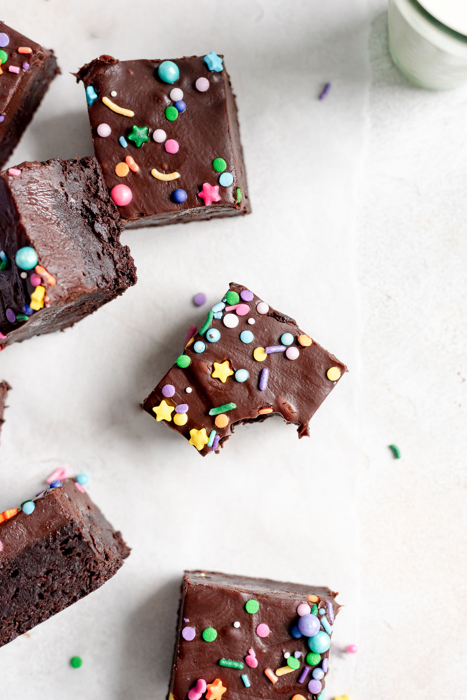 overhead shot of brownies scattered on table one with bite missing